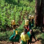 The Water Project: Jidereri Primary School -  Carrying Water Back To School