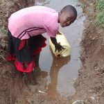 The Water Project: Jivovoli Community A -  Fetching Water From Spring Overflow