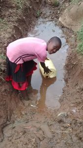 The Water Project:  Fetching Water From Spring Overflow
