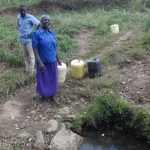 The Water Project: Ingavira Community, Laban Mwanzo Spring -  Fetching Water