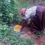 The Water Project: Koloch Community, Solomon Pendi Spring -  Mrs Pendi Fetching Water