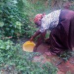 The Water Project: Koloch Community -  Mrs Pendi Fetching Water