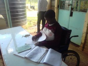 The Water Project:  Student Studying By The Plastic Tank