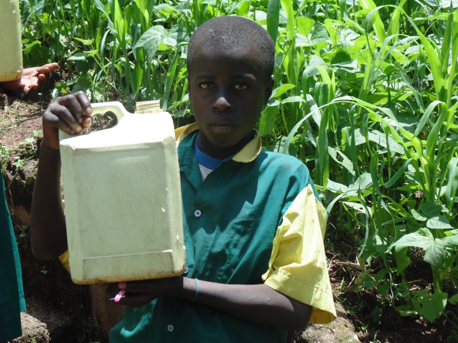 The Water Project : kenya18065-boy-holds-up-container-filled-with-water