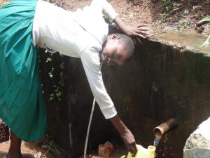 The Water Project:  Girl Fills Jerrycan At Spring