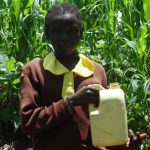The Water Project: Gemeni Salvation Primary School -  Girl Holds Up Container With Water