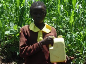 The Water Project:  Girl Holds Up Container With Water