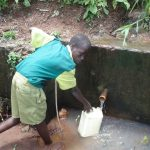The Water Project: Gemeni Salvation Primary School -  Student Fetch Water From A Nearby Spring