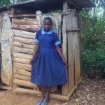 The Water Project: Shihimba Primary School -  Girl In Front Of Latrine
