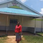 The Water Project: Precious School Kapsambo Secondary -  Madam Jesicah Demesi Standing Next To The Girls Dormitry Named After Her As The Pioneer Of The Girls Education