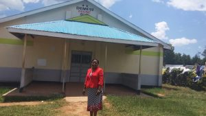 The Water Project:  Madam Jesicah Demesi Standing Next To The Girls Dormitry Named After Her As The Pioneer Of The Girls Education