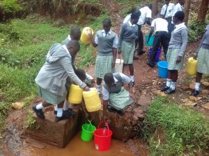 The Water Project:  Students Collect Water From Protected Spring