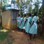 The Water Project: Eshisenye Primary School -  Girls Line Up To Use Latrine
