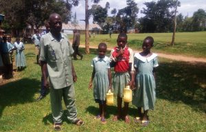 The Water Project:  Schools Teacher Poses With Students At The School