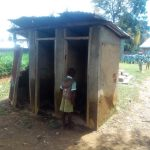 The Water Project: Eshisenye Primary School -  Student Looks Inside Broken Latrine