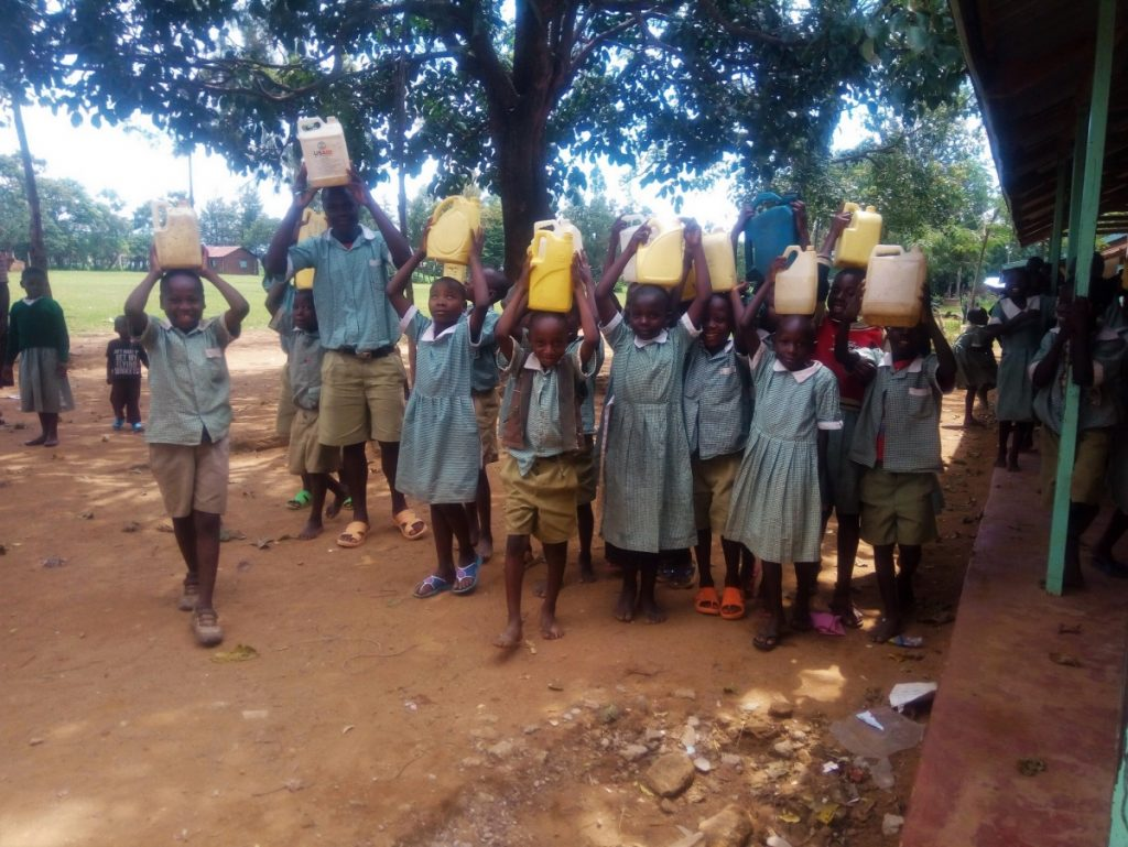 The Water Project : kenya18078-students-hold-jerrycans-and-water-containers-atop-their-heads