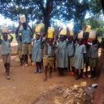 The Water Project: Eshisenye Primary School -  Students Hold Jerrycans And Water Containers Atop Their Heads