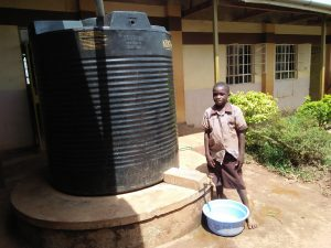 The Water Project:  Student Stands At Rainwater Tank