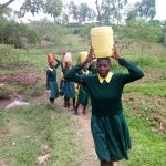 The Water Project: Imbale Primary School -  Girls Carry Water On Their Heads