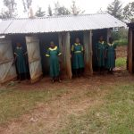 The Water Project: Imbale Primary School -  Girls Pose Infront Of Latrines