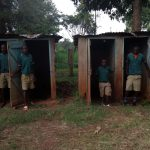 The Water Project: Imbale Primary School -  Students Stand In Latrines