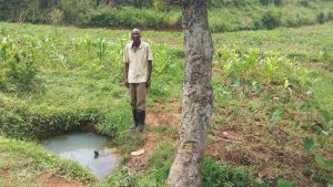 The Water Project:  Man Stands Next To Spring