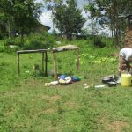The Water Project: Luvambo Community B -  A Lady Washes Utencils Outside Her Home