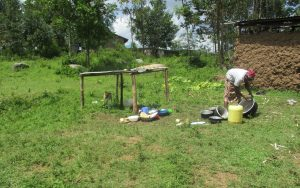 The Water Project:  A Lady Washes Utencils Outside Her Home