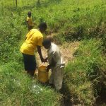 The Water Project: Emachembe Community -  A Son Helping Her Mother Carry Water From The Spring