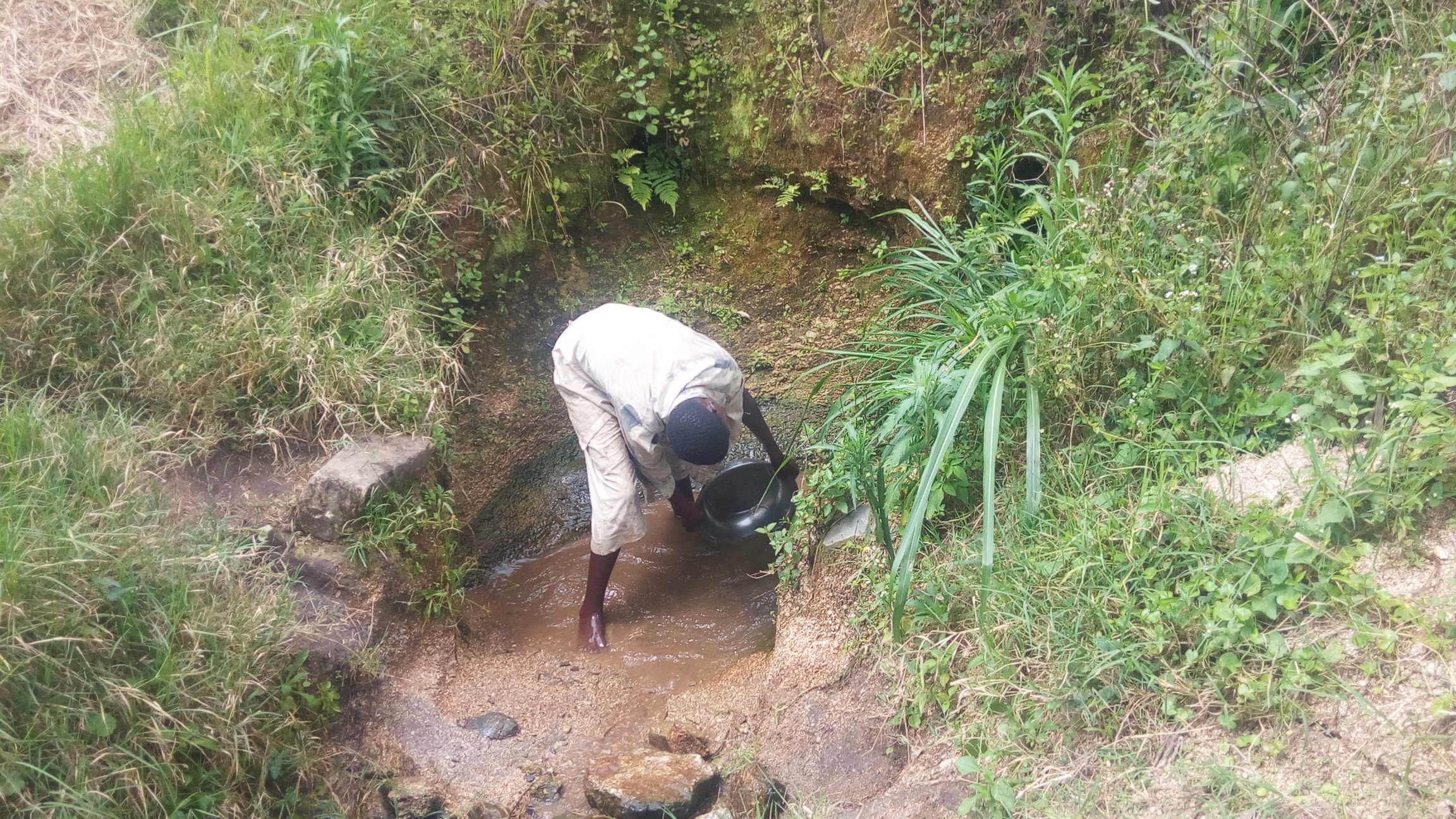 The Water Project : kenya18138-clearing-spring-to-determine-actual-source-of-water