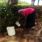 The Water Project: Mungaha B Community, Maria Spring -  Gather Water In Small Containter To Pour Into Larger Bucket