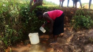 The Water Project:  Gather Water In Small Containter To Pour Into Larger Bucket