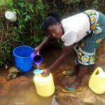 The Water Project: Mungaha B Community, Maria Spring -  Woman Filters Water Into Jerrycan
