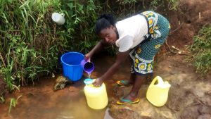The Water Project:  Woman Filters Water Into Jerrycan