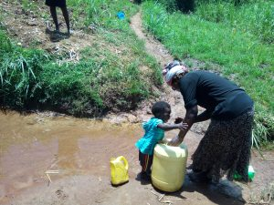 The Water Project:  Child Plays As His Mother Collects Water
