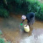 The Water Project: Chegulo Community, Yeni Spring -  Filling Smaller Cup To Top Off Jerrycan
