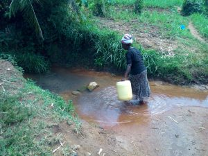 The Water Project:  Trudging Into Water Source For Collection