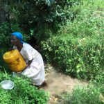 The Water Project: Muyundi Community A -  A Lady Struggles To Lift A Water Container At The Spring