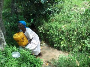 The Water Project:  A Lady Struggles To Lift A Water Container At The Spring