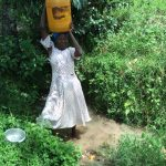 The Water Project: Muyundi Community, Ngalame Spring -  Hoisting Jerrycan Of Water Onto Head