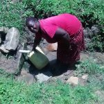 The Water Project: Ewamakhumbi Community, Yanga Spring -  Woman Fetches Water From The Spring