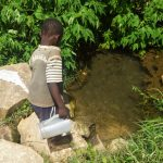 The Water Project: Emachembe Community A -  Boy Fetches Water From Spring