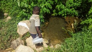The Water Project:  Boy Fetches Water From Spring