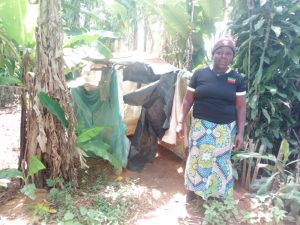 The Water Project:  Woman Stands Next To Improvised Latrine