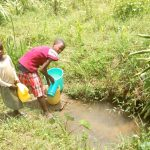 The Water Project: Emaka Community -  Children From The Community Fetching Water At Anuka Unprotected Spring