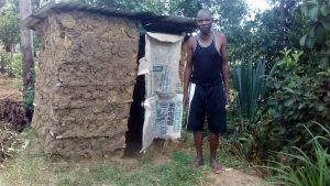 The Water Project:  A Community Member Stands By His Temporal Latrine