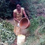 The Water Project: Lunyi Community, Fedha Mukhwana Spring -  Woman Pours Water Into Jerrycan