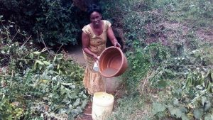 The Water Project:  Woman Pours Water Into Jerrycan