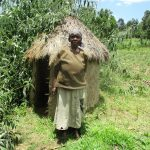 The Water Project: Shirugu Community, Jeremiah Mashele Spring -  Belinda Ogutu A Water User Stands Beside Her Grass Thatched Latrine