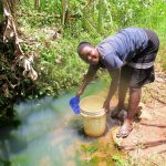The Water Project: Shirugu Community, Jeremiah Mashele Spring -  Filling Container With Water